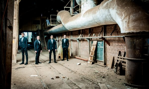 THE JENGLERS wearing suits in old factory on second promotion picture done by John Alexander Bell in October 2019