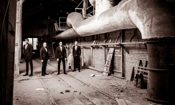THE JENGLERS wearing suits in old factory on second promotion picture in sepia done by John Alexander Bell in October 2019