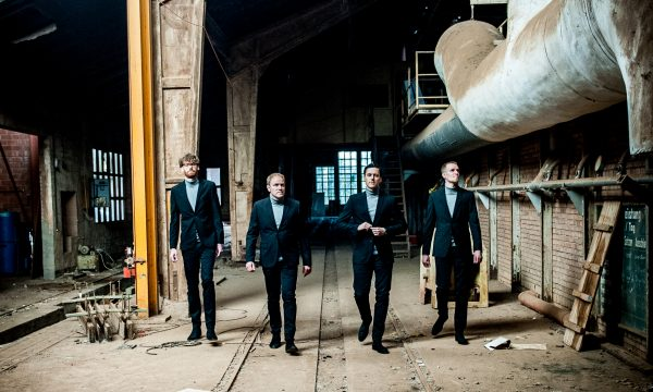 THE JENGLERS wearing suits and walking in old factory on third promotion picture done by John Alexander Bell in October 2019