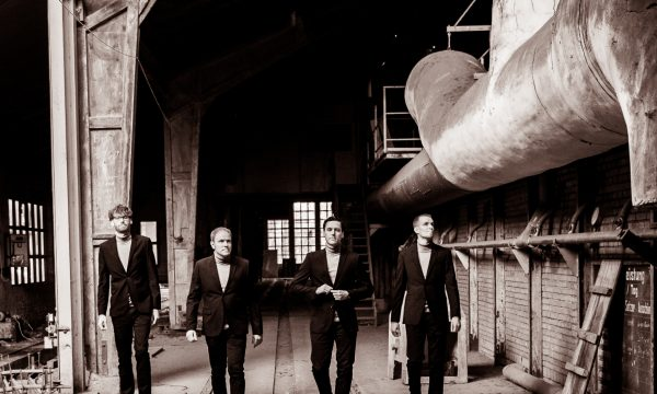 THE JENGLERS wearing suits and walking in old factory on third promotion picture in sepia done by John Alexander Bell in October 2019